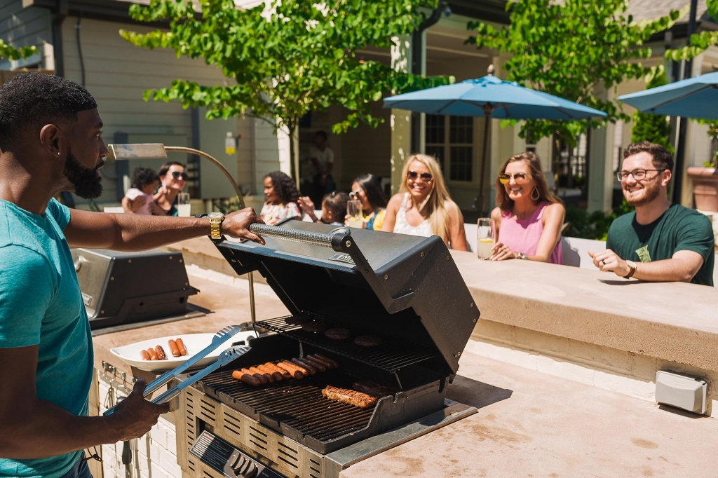 image of residents enjoying community amenities outside such as a barbecue grill and shade umbrellas